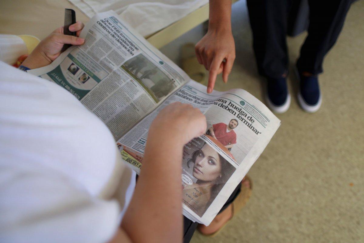 新聞を読む拘留者